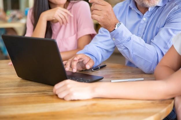 Reunión del equipo empresarial en una computadora portátil abierta, viendo presentaciones, hablando, discutiendo y compartiendo ideas
