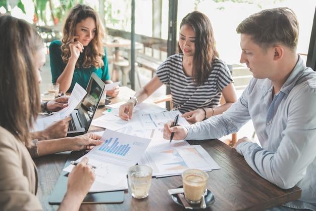 Reunión de equipo empresarial diverso en una cafetería
