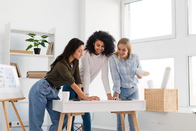 Reunión del equipo de mujeres de alto ángulo en la oficina