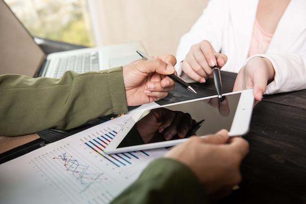 Reunión del equipo de negocios para discutir los datos estadísticos presentados en forma de gráficos y tablas digitales.