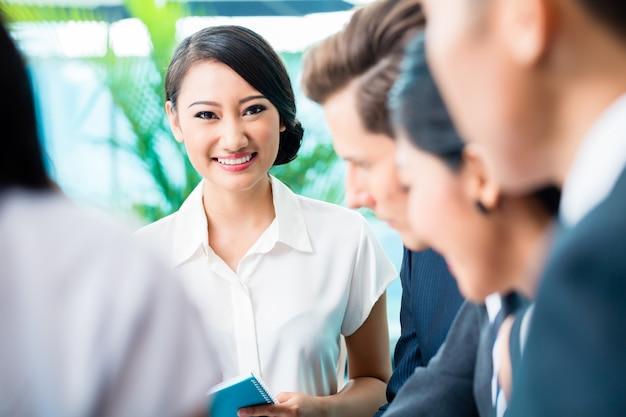 Reunión del equipo de negocios de ejecutivos asiáticos y caucásicos.