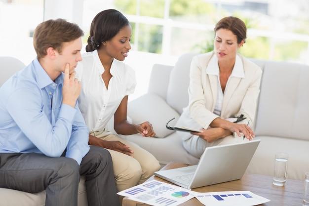 Reunión del equipo de negocios para pasar las cifras en el sofá