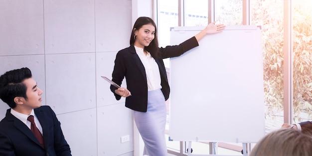Reunión de equipo de negocios y presente proyecto en oficina blanca.