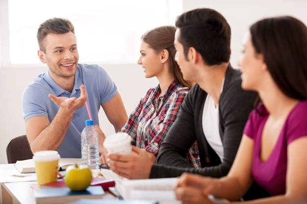 Reunión de estudiantes. cuatro estudiantes alegres hablando entre sí mientras están sentados en el escritorio