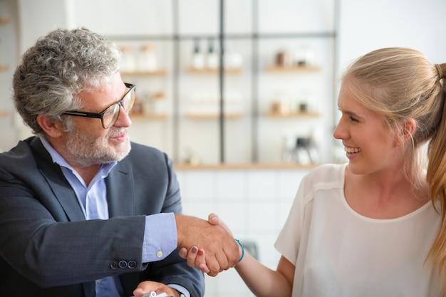 Reunión exitosa de jóvenes emprendedores con inversionistas maduros en el trabajo conjunto