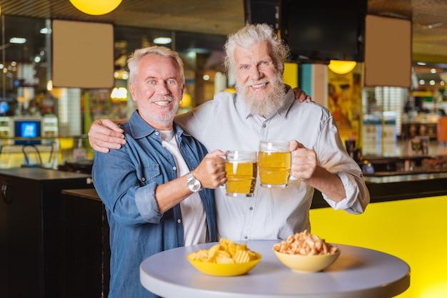 Reunión familiar. hombres agradables felices mirándote mientras está de pie junto con vasos de cerveza