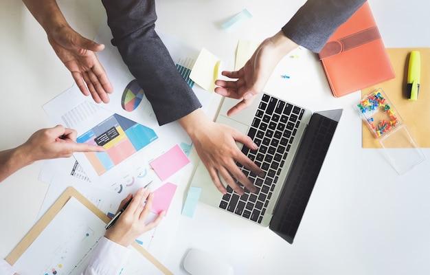 Reunión de gente de negocios usando computadora portátil y papel de gráfico del mercado de valores para el análisis.