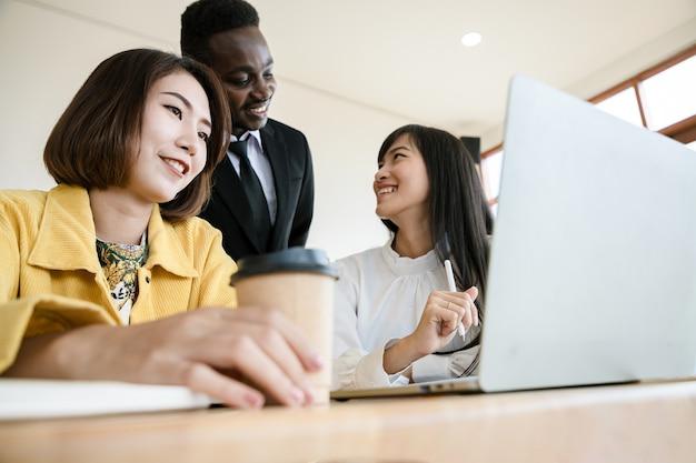 Reunión de grupo de jóvenes empresarios y creación de acuerdos sobre laptop en la organización. líder de empresario en la oficina. proyectos exitosos y felicitaciones.