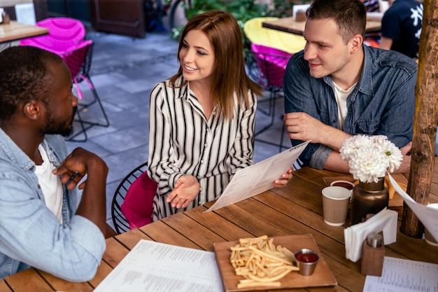 Reunión informal de estudiantes en el acogedor café en el día soleado.