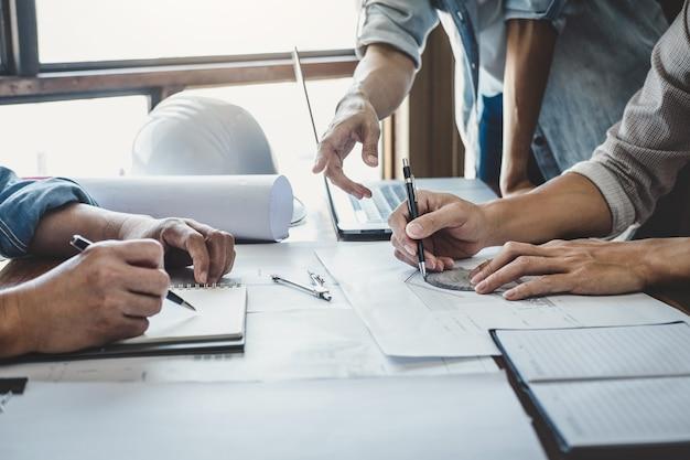 Reunión de ingenieros para el proyecto de trabajo con socios y herramientas en construcción de modelos y planos