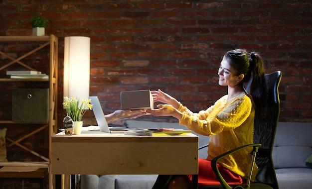 Reunión en línea, chat, videollamada. mujer joven hablando con un amigo en línea a través de la computadora portátil en casa. realidad virtual. concepto de entretenimiento remoto seguro, reuniones durante la cuarentena. copia espacio