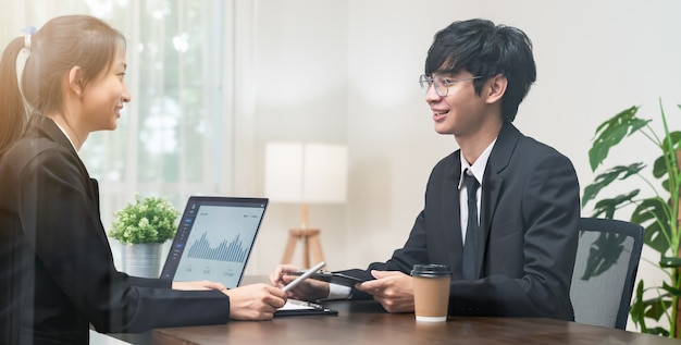 Reunión de lluvia de ideas de trabajo en equipo y nuevo proyecto de inicio en el lugar de trabajo, empresarios asiáticos sonrientes que trabajan en una computadora portátil con documentos gráficos.