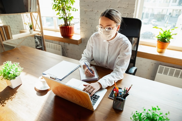 Reunión. mujer que trabaja sola en la oficina durante la cuarentena por coronavirus o covid-19, con mascarilla. joven empresaria, gerente haciendo tareas con teléfono inteligente, computadora portátil, tableta tiene conferencia en línea.