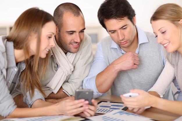Reunión de negocios alrededor de la mesa con dispositivos electrónicos.