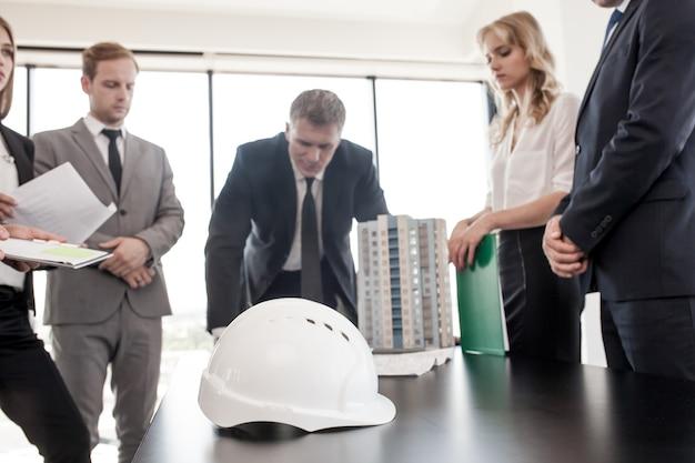 Reunión de negocios de arquitectos e inversores mirando el modelo de casa de edificio residencial de varios pisos moderno en la mesa