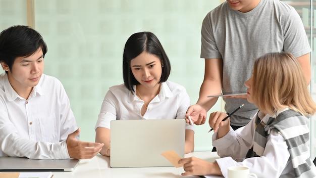 Reunión de negocios de inicio, jóvenes motivados hablando y reunidos en el lugar de trabajo de oficina.
