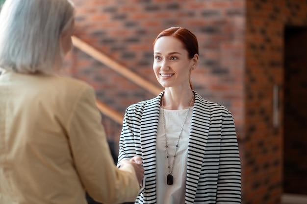 Reunión de negocios. joven empresaria pelirroja un apretón de manos con su colega senior en una reunión informal