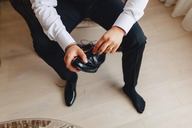Reunión del novio, detalles, chaqueta, zapatos, relojes y botones en el día de la boda.