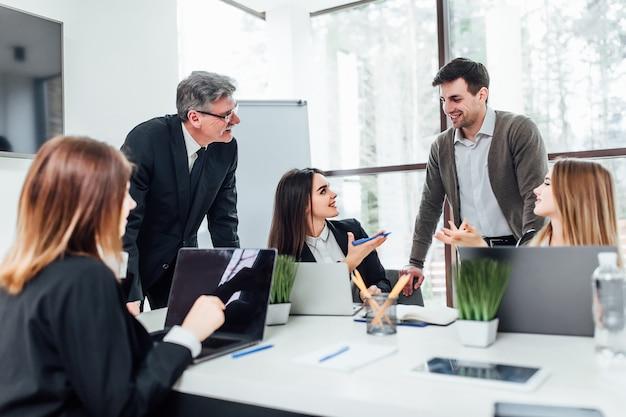 Reunión de personal. grupo de cinco jóvenes modernos en ropa casual elegante discutiendo algo mientras trabajaba en la oficina creativa.