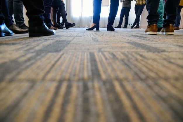 La reunión de personas, con una mujer líder, solo ve los pies sobre la alfombra.