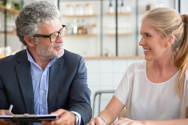 Reunión profesional madura con cliente joven en coworking, sosteniendo documentos, hablando y riendo