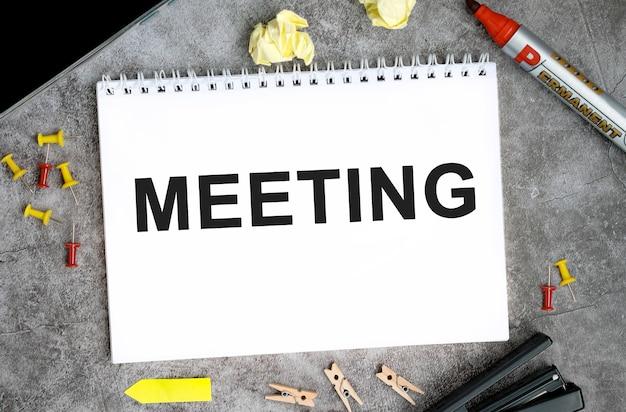 Reunión de texto en un cuaderno blanco con alfileres, marcador y grapadora en una mesa de hormigón