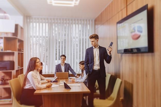 Reunión de trabajadores de oficina en la mesa, mirando la presentación con diagramas en el televisor.