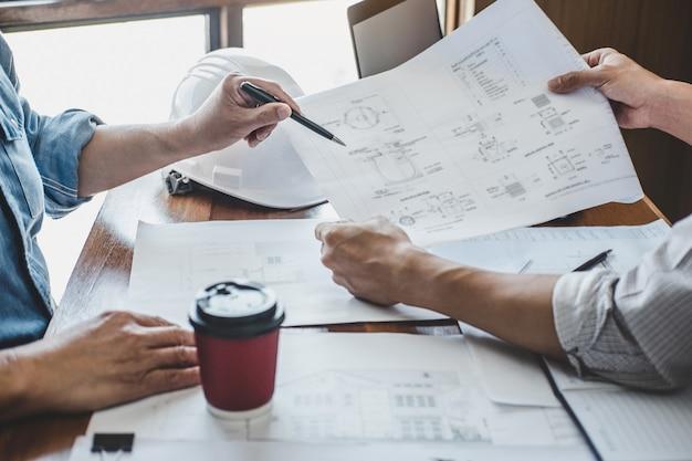 Reunión de trabajo en equipo de ingenieros, dibujo trabajando en la reunión de planos para el proyecto que trabaja con un socio en la construcción de modelos y herramientas de ingeniería en el sitio de trabajo, concepto de construcción y estructura.