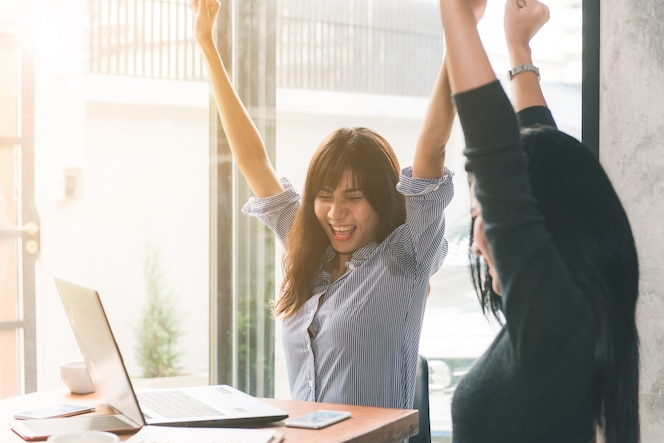 Reunión uno-a-uno. dos jóvenes empresarias sentados a la mesa en el café. la muchacha muestra información del colega en la pantalla de la computadora portátil. chica con smartphone blogging. reunión de trabajo en equipo. trabajadores independientes trabajando.