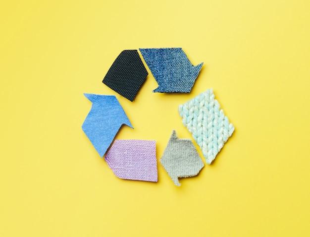 Reutilizar, reducir, reciclar el concepto de fondo. símbolo de reciclaje hecho de ropa vieja sobre fondo amarillo.