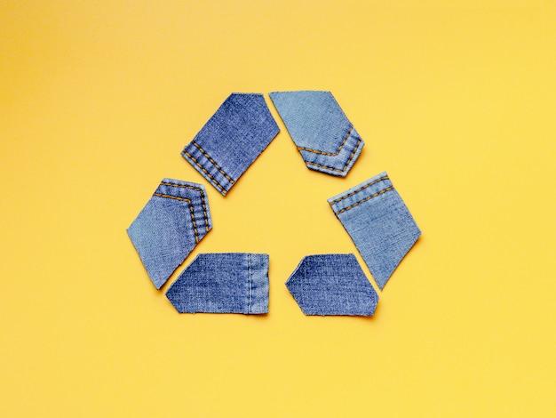 Reutilizar, reducir, reciclar el concepto de fondo. símbolo de reciclaje de jeans viejos sobre fondo amarillo.