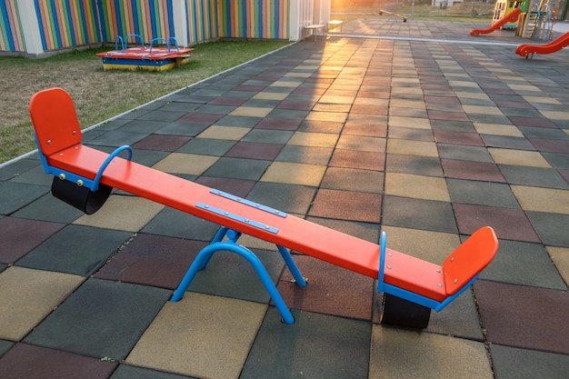 El revestimiento de goma y la tapa abatible se balancean en el patio de recreo en el preescolar.