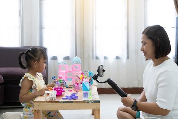 Revisión de la madre y la hija jugando juguetes en casa. con grabación haciendo video.