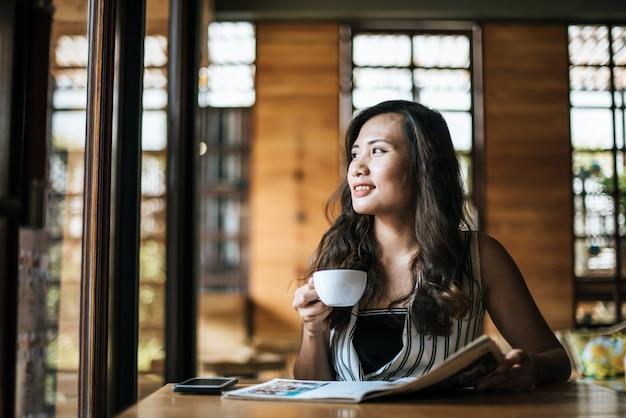 Revista hermosa de la lectura de la mujer en café