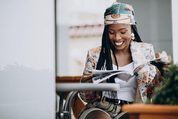 Revista de lectura de mujer afroamericana en un café