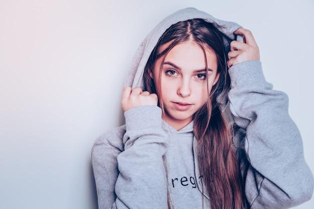 Revista de moda. encantadora joven que trabaja como modelo para la línea de moda adolescente y muestra una sudadera con capucha gris