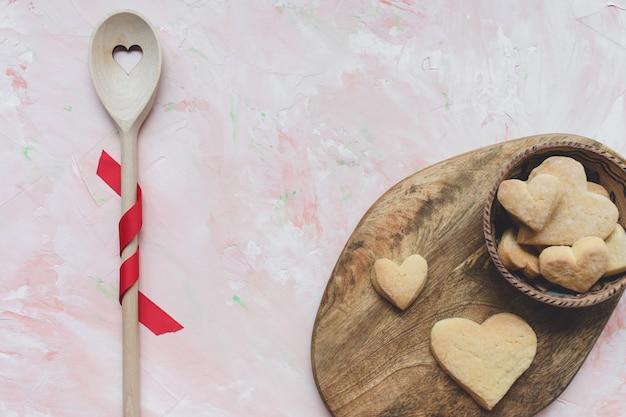 Revolviendo la cuchara y las galletas de mantequilla en forma de corazón sobre un fondo rosa