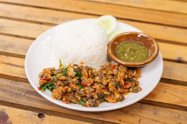 Revuelva el berberecho frito con albahaca servido con arroz cocido.
