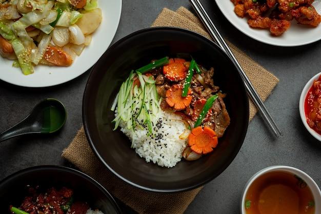 Revuelva el cerdo frito con salsa coreana sobre fondo oscuro