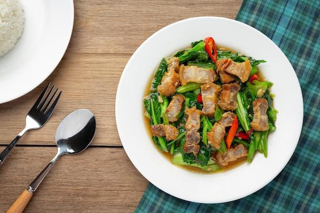 Revuelva la col rizada frita, cerdo crujiente picante en la mesa de madera concepto de comida tailandesa.