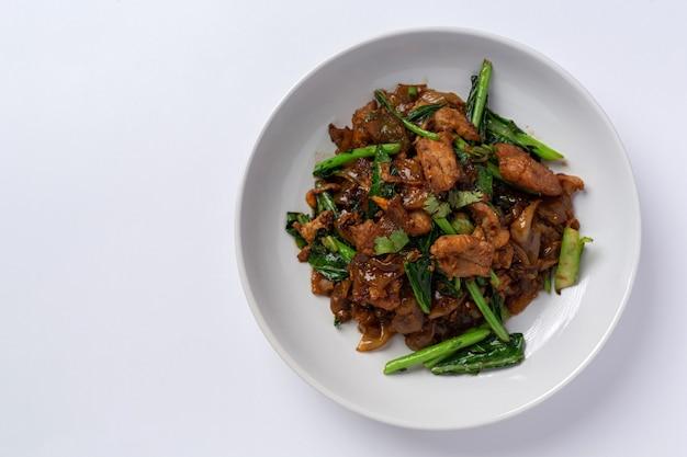 Revuelva los fideos de arroz fritos con salsa de soja y carne de cerdo sobre fondo blanco.