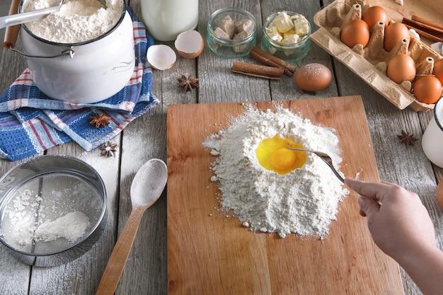 Revuelva la masa. cartón de harina, leche, mantequilla, levadura, especias y huevos en la mesa de madera rústica, ingredientes para cocinar. mujer chef panadero pov