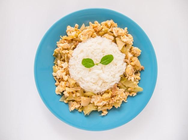 Revuelva los pepinillos y los huevos fritos con arroz en un plato azul