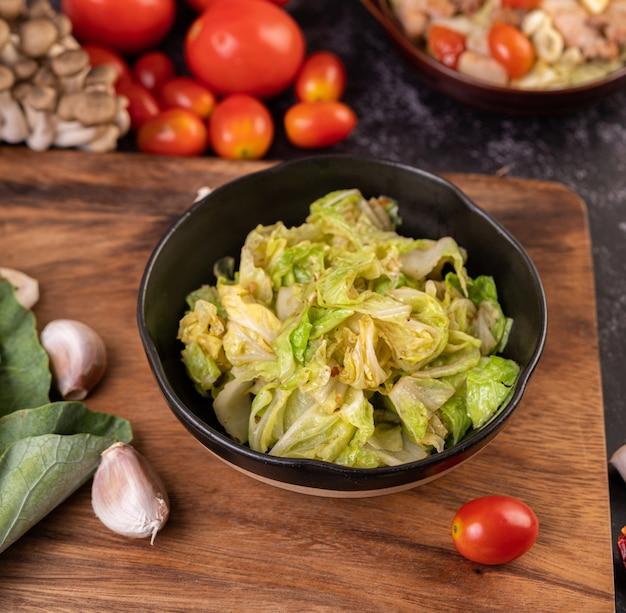 Revuelva el repollo blanco con salsa de ostras en un plato negro.