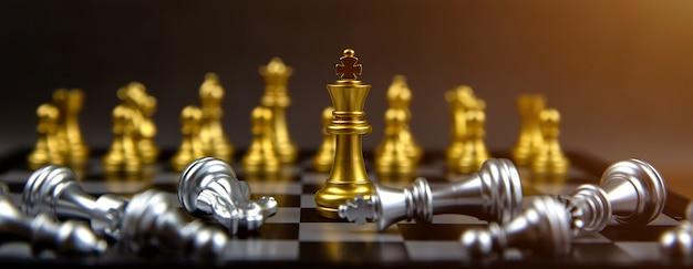 El rey del ajedrez dorado parado en medio de la caída del ajedrez plateado. conceptos de liderazgo y planes de estrategia empresarial.