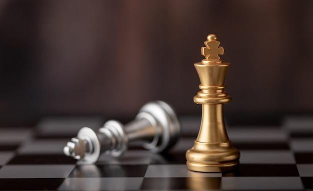 Rey de oro de pie y cayendo sobre el tablero de ajedrez