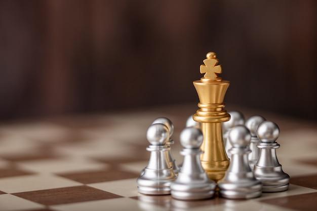 Rey de oro de pie en medio del ajedrez a bordo