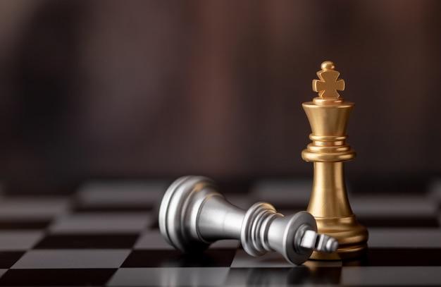 Rey de oro de pie y plata cayendo sobre tablero de ajedrez.