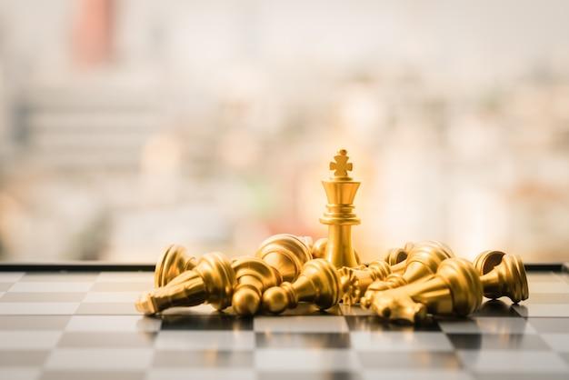 Rey de oro y plata de ajedrez en el fondo de la ciudad.