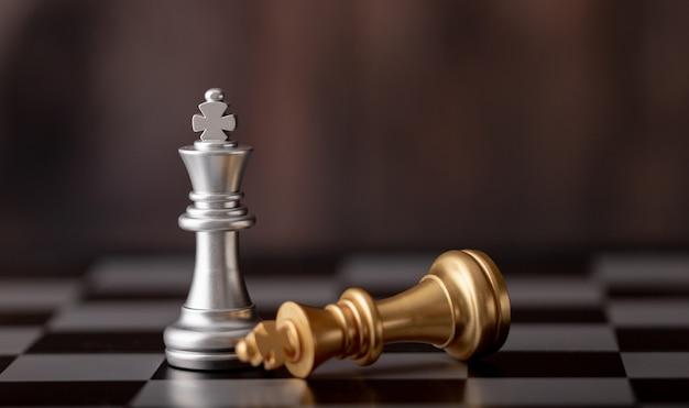 Rey de plata de pie y oro cayendo sobre tablero de ajedrez